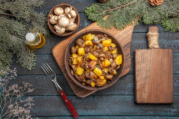 Top view plate and cutting board potatoes and mushrooms in bowl on brown board next to the fork and wooden cutting board under bowl of mushrooms oil in bottle and branches with cones