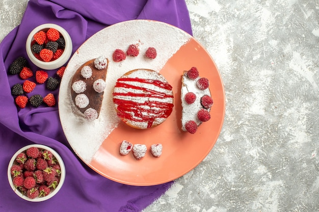 Top view of plate of dessert on purple napkin with berries on side on marble background