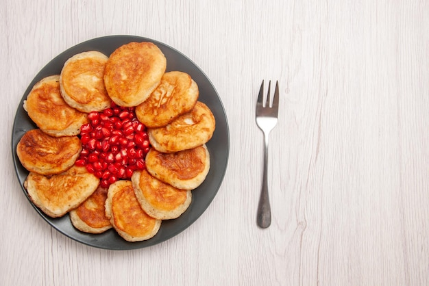 Top view plate of dessert seeds of red pomegranate and pancakes on the black plate next to the fork on the white background