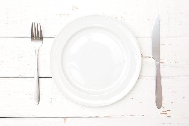 Top view of plate, fork and knife on wooden background