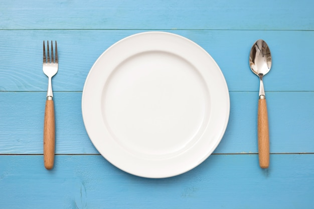 Top view of plate, fork and spoon on wooden background