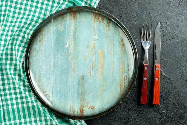トップビュープレート緑と白の市松模様のテーブルクロスナイフと黒のテーブルのフォーク