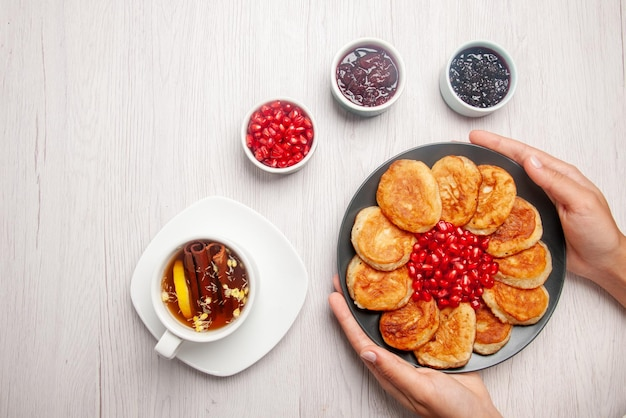 Top view plate in hands bowls of jam a cup of tea with lemon and plate of pancakes and pomegranate in hands on the table