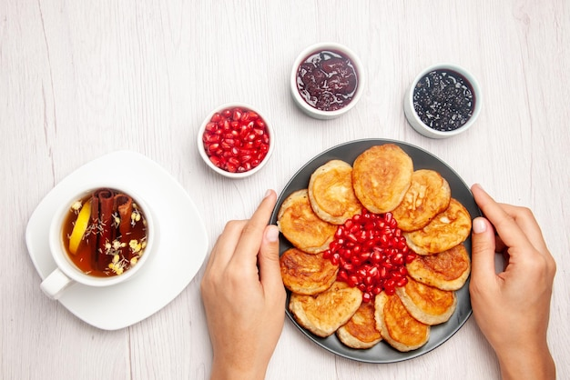 Top view plate in hands white cup of tea with cinnamon sticks bowls of jam and plate of pancakes and pomegranate in hands on the table