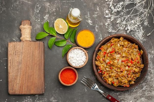 豆とスパイスのトップビュープレートカラフルなスパイスのボウルは、暗いテーブルの上のまな板のオイルとフォークの横にある緑色の豆のプレートをレモンします
