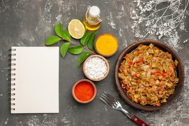 豆とスパイスのトップビュープレートカラフルなスパイスのボウルレモンホワイトノートブック暗いテーブルの上のオイルとフォークのボトルの横にある緑色の豆のプレート