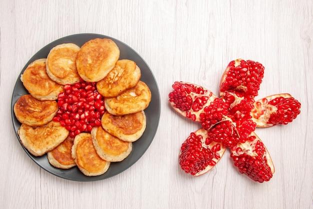 Тарелка десертных семян красного граната и блины на черной тарелке рядом с очищенным гранатом на белой поверхности вид сверху