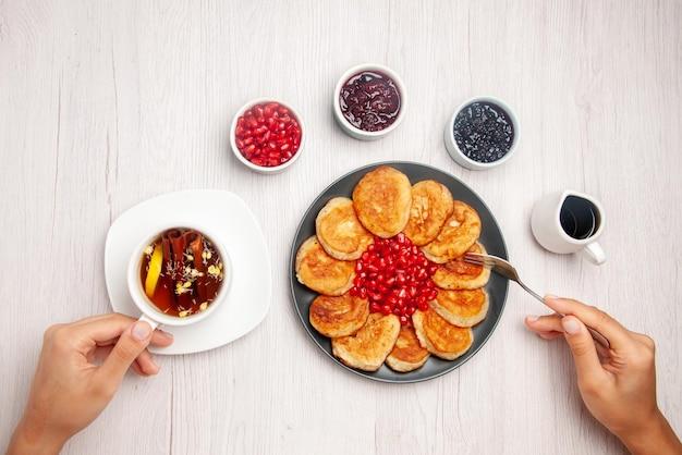 흰색 테이블에 있는 탑 뷰 플레이트 잼과 팬케이크와 포크의 소스 플레이트, 손에 홍차 한 잔, 테이블에 레몬이 든 허브 차 한 잔