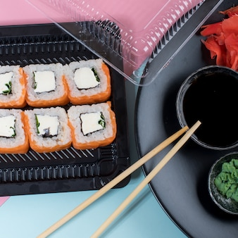Top view on the plate of rolls with pink cream and philadelphia roll