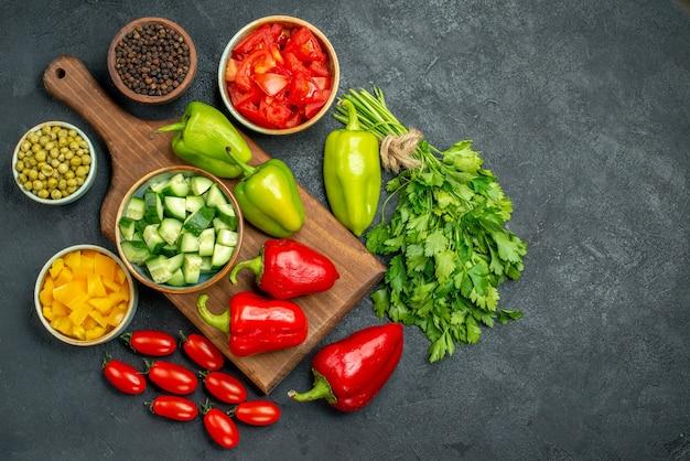 Vista dall'alto del supporto del piatto con verdure sopra e vicino ad esso e con spazio libero per il testo su sfondo grigio scuro