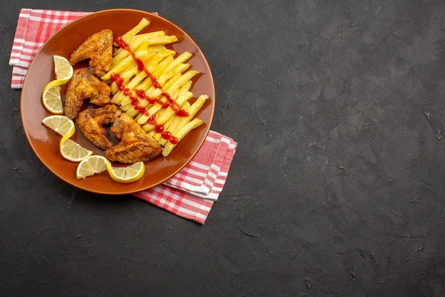 Top view plate on tablecloth orange plate of appetizing french fries chicken wings ketchup and lemon on pink-white checkered tablecloth on the left side of the dark table