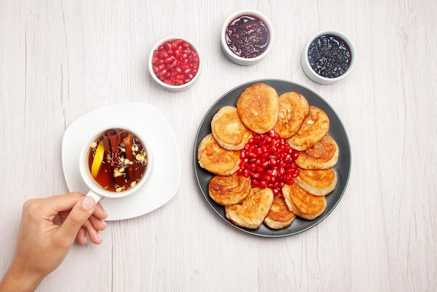 Top view plate on the white table bowls of jam plate of pancakes and white cup of tea with cinnamon sticks in hands on the table