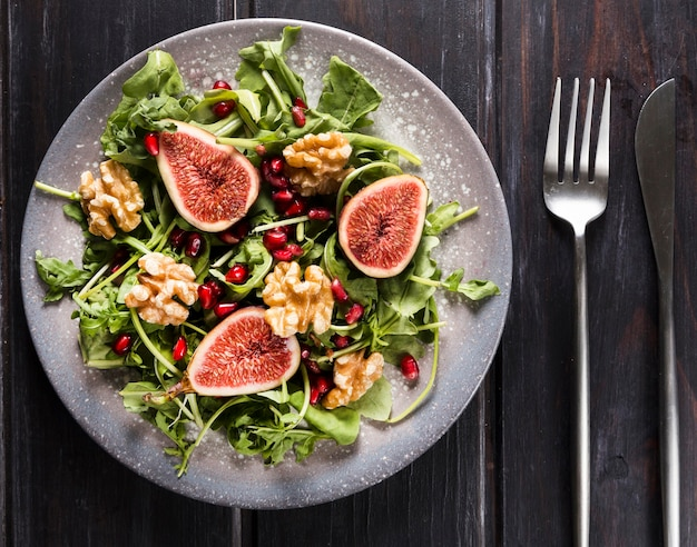 Top view of plate with autumn fig salad and cutlery