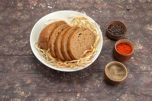 Вид сверху тарелка с хлебом и приправами на коричневом, пищевое тесто