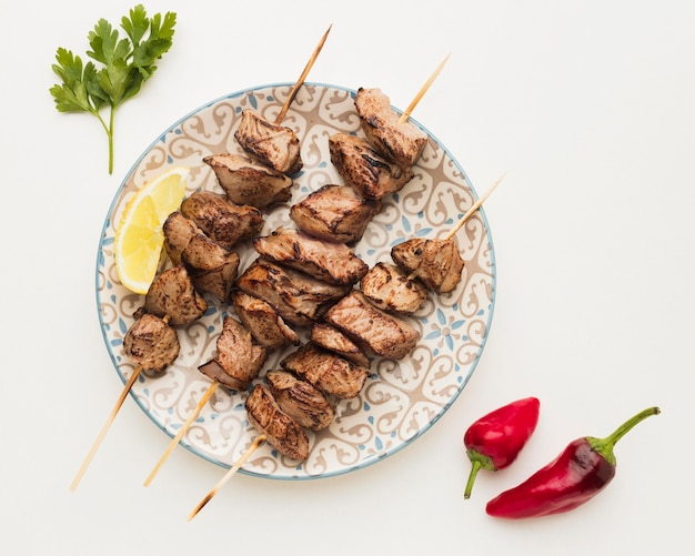 Top view of plate with delicious kebab and chili peppers