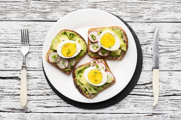Top view of plate with egg and avocado sandwiches and cutlery