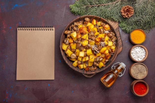 튀긴 버섯과 감자 다채로운 향신료 오일과 콘이 있는 나뭇가지 옆에 있는 노트북이 있는 음식 접시가 있는 탑 뷰 플레이트