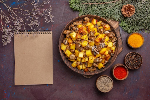 Piatto vista dall'alto con piatto di cibo con patate fritte e taccuino di funghi e spezie diverse accanto ai rami e ai coni di abete