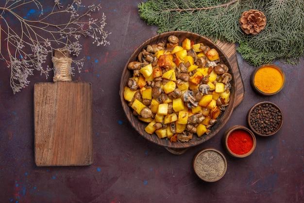 전나무 가지와 원뿔 옆에 버섯 도마와 다른 향신료가 있는 튀긴 감자가 있는 음식 접시가 있는 탑 뷰 플레이트