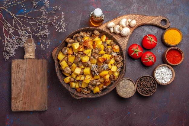 きのことジャガイモの油をボトルに入れたフードプレートとトップビュープレートトマトきのこカラフルなスパイスとまな板