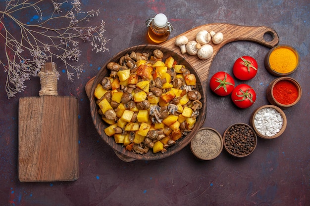 Top view plate with food plate with mushrooms and potatoes oil in bottle tomatoes mushrooms colorful spices and cutting board