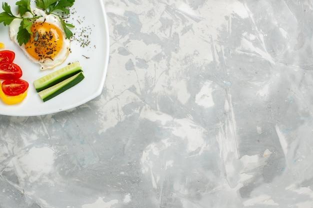 ライトホワイトのデスクに野菜と緑のトップビュープレート野菜料理食事ランチカラー写真