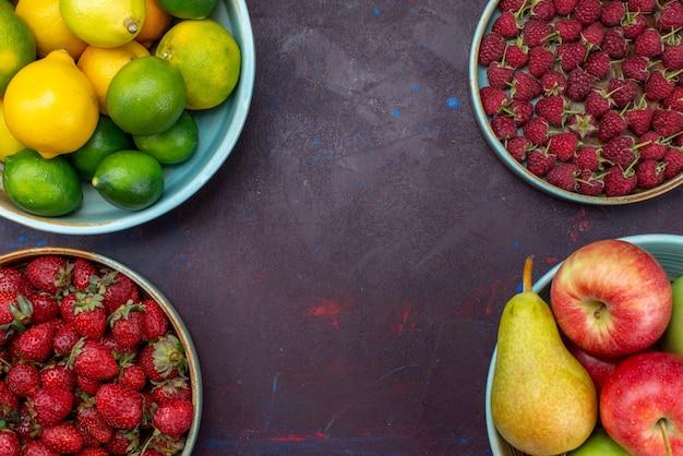 暗い机の上に柑橘類とベリーとフルーツ梨とリンゴのトップビュープレート