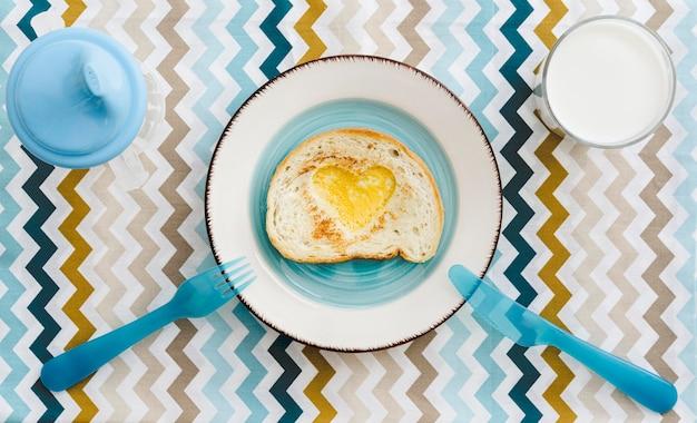 Вид сверху тарелка с яйцом в форме сердца для ребенка