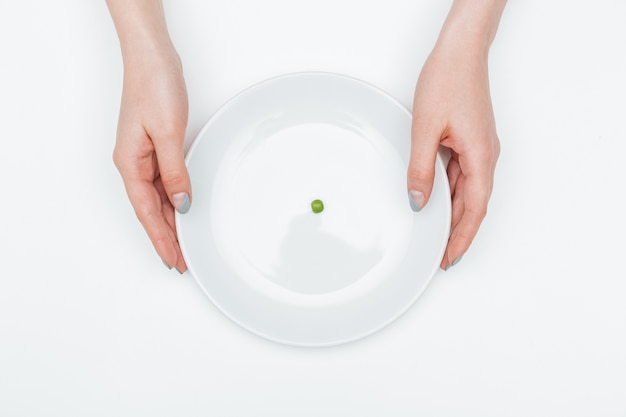 Top view of plate with one small green pea holded by hands of young woman