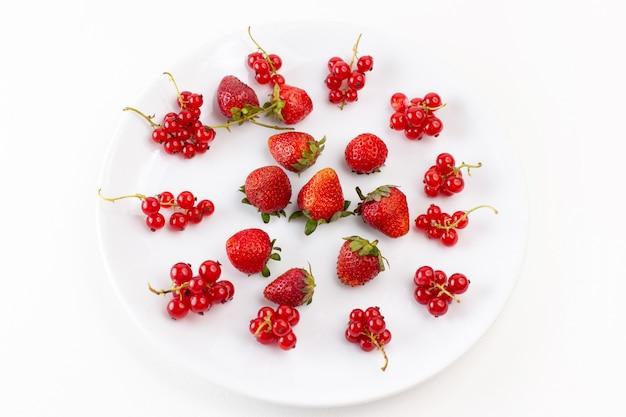 Вид сверху тарелка с клубникой, свежей и спелой на белом фоне, цвет свежих спелых фруктовых ягод