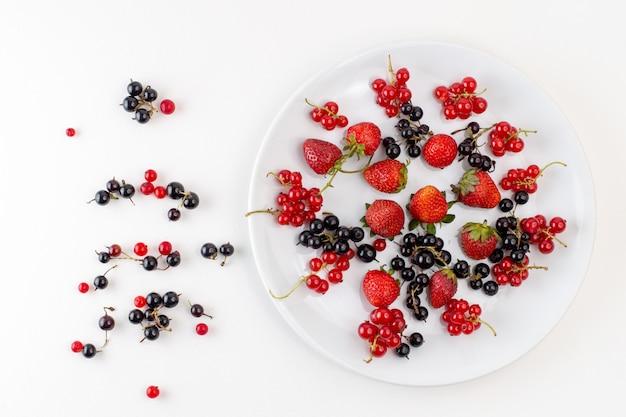 Вид сверху тарелка с клубникой, свежей и спелой, с черникой и клюквой на белом фоне, цвет свежих спелых фруктовых ягод