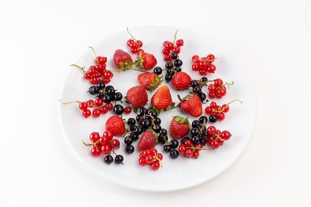 Вид сверху тарелка с клубникой, свежей и спелой с черникой на белом фоне, цвет свежих спелых фруктовых ягод