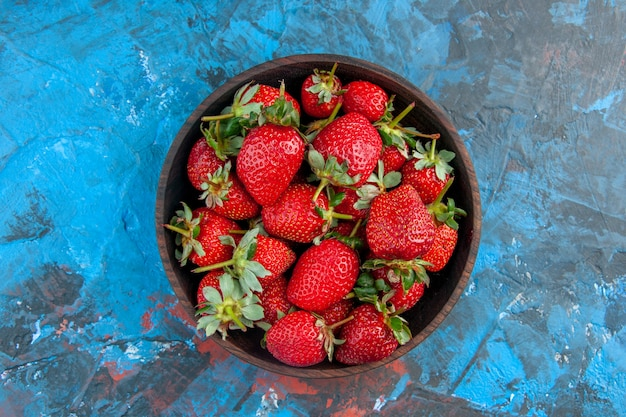 Piatto vista dall'alto con fragole fresche e gustose frutti maturi su sfondo blu