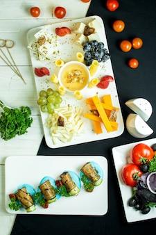 Vista dall'alto di un piatto con vari formaggi uva e miele
