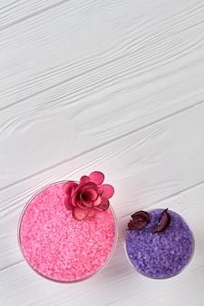 꽃과 함께 분홍색과 파란색 바다 소금의 상위 뷰 접시