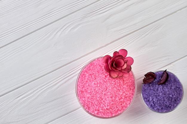 분홍색과 보라색 스파 소금과 꽃의 상위 뷰 플레이트