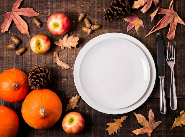 Top view of plates for thanksgiving dinner with autumn leaves