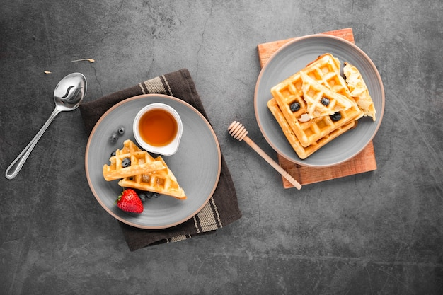 Top view plates with waffles and fruits