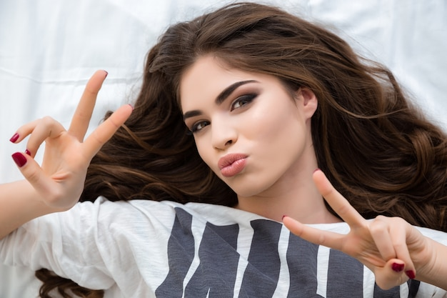 Top view of playful beautiful young woman lying and showing peace sign over white background