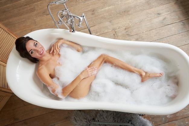 Вид сверху. приятная женщина, получающая удовольствие в пенной ванне
