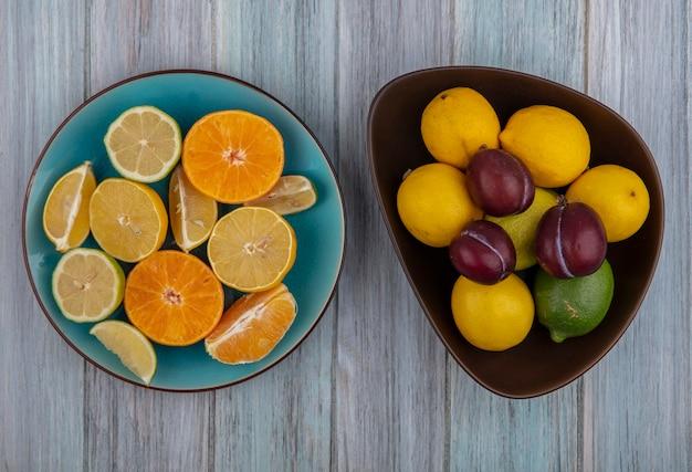 Вид сверху сливы в миске с дольками лимона, лаймом и апельсином на тарелке на сером фоне