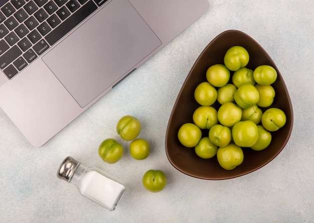 Top view of plums in bowl and salt with note book on white background
