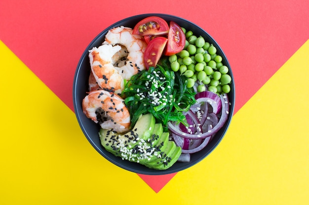 Top view of poke bowl with red shrimps and vegetables