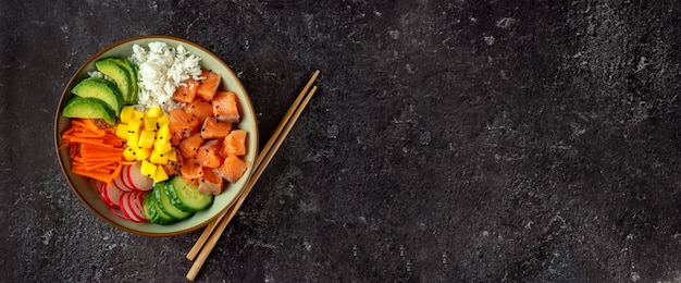 Top view of poke bowl with salmon and avocado on dark table, copyspace
