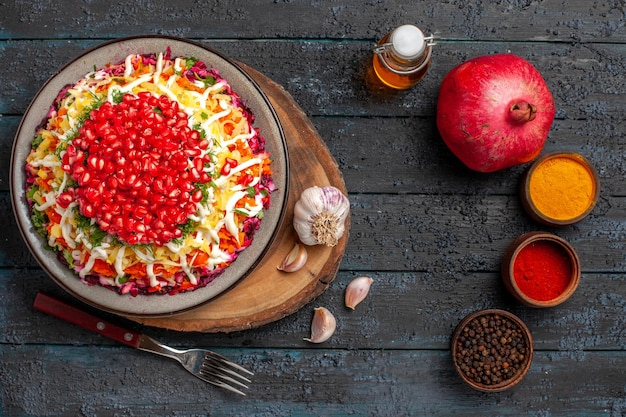 Вид сверху гранатовое аппетитное блюдо из граната в тарелке и чеснок на разделочной доске рядом с бутылкой различных специй, масляной вилкой и гранатом