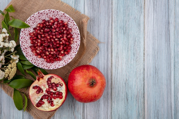Top view of pomegranate berries in bowl with whole and half ones with flowers on wooden surface