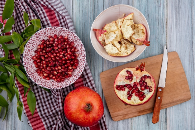 Top view of pomegranate berries in bowl with whole one and leaves on plaid cloth and half one with knife on cutting board with bowl of pomegranate shell on wooden surface