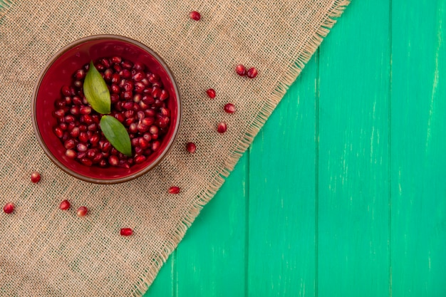 Top view of pomegranate berries with leaves in bowl and on sackcloth on green surface