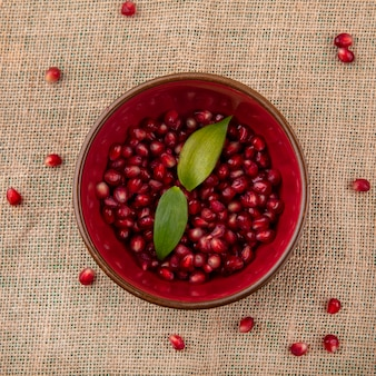 Top view of pomegranate berries with leaves in bowl and on sackcloth surface