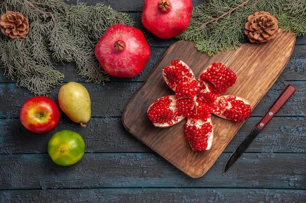 Vista dall'alto melograno a bordo melograno pilled sul tagliere accanto a rami di abete rosso con coni coltello lime pera mela su superficie grigia